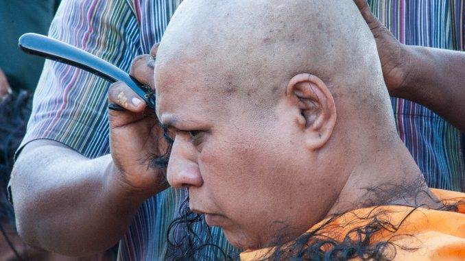 man getting head shaved at Thaipusam