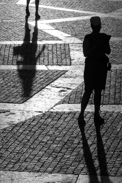 Black and white photo of people and their shadows by Piero Leonardi