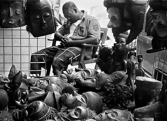 Black and White Inspired Photography: man sleeping in his booth full of masks in New York Ciy by Jim Austin.