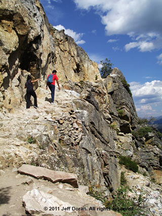 Image of hikers on a rock ledge at Inspiration Point, Grand Tetons, Wyoming by Jeff Doran.