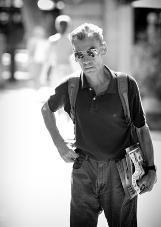 Black and white portrait of gray-haired man with sunglasses on the street by Alex Lagarejos.