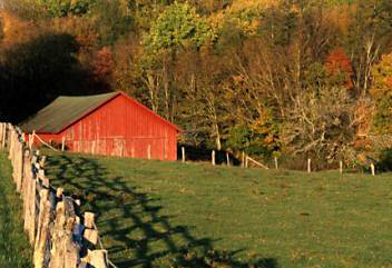 Wooden fence and shadows leading the eye to a red barn by Andy Long.
