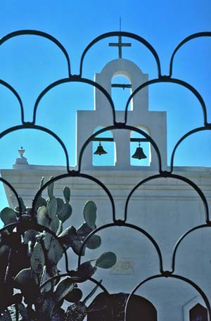 Image of San Xavier del Bac Mission taken through an ornate gate by Mike Goldstein.