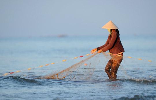 Photo of woman fishing in Mui-Ne, Vietnam by Ron Veto