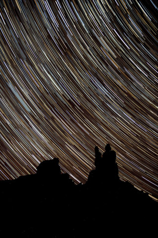 Star Trails photography: star trails over silhouetted rock formations at Valley of the Gods, Utah by Andy Long.