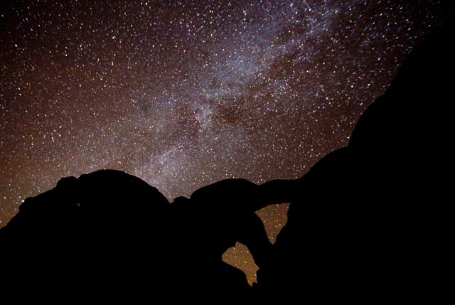 Star photography: Milky Way and lots of stars with silhouetted rock formations in foreground at Arches National Park, Utah by Andy Long.