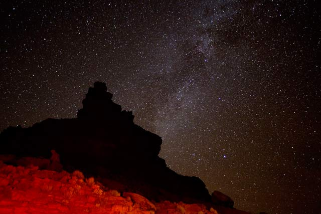Star photography: flashlight on foreground rock formations and stars at Valley of the Gods, Utah by Andy Long.