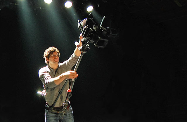 Product Review of hipjib. Man with hipjib around his waist - booming with an extended tripod and video camera.