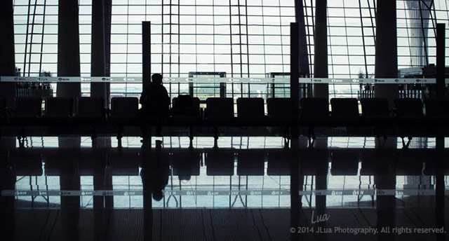 """Ready for Flight"": reflections at Beijing Capital International Airport of a person, chairs and surroundings by Jean Lua."