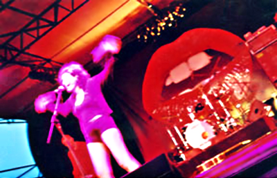 Color image make with slowe shutter speed of Deborah Conway performing on stage by Lisa J. Young.