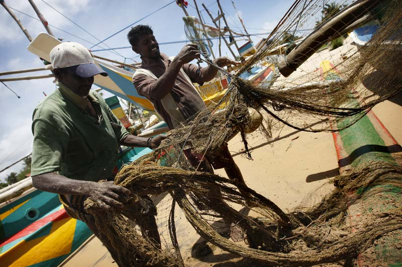 Photo of men repairing fishing nets in Hikkaduwa by Marielle van Uitert