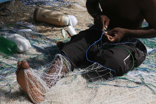 Photo of man repairing fishing net by Marielle van Uitert