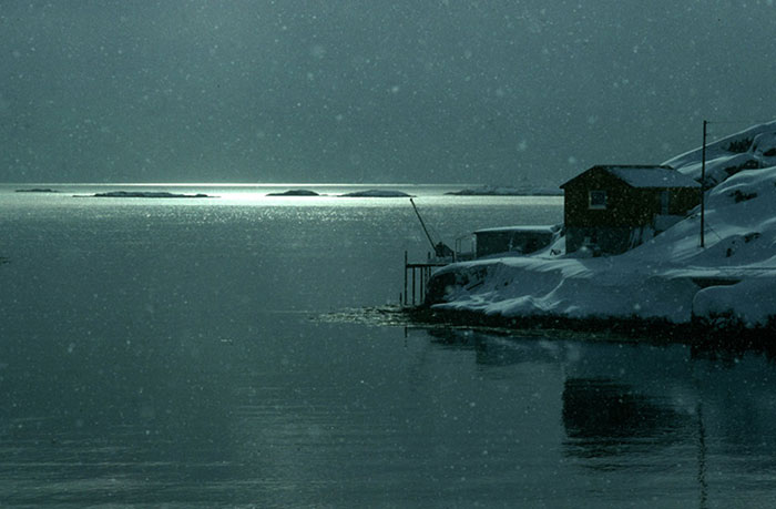 Winter photo of cabin on shore in Norway by Gert Wagner