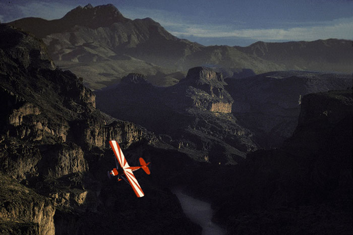 Photo of small plane flying over mountainous Sonora Desert, Arizona by Gert Wagner