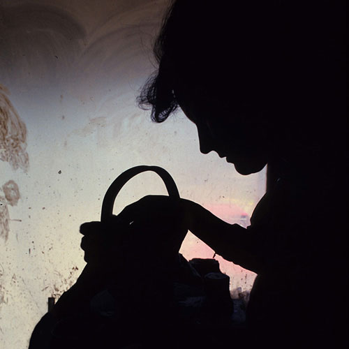 Silhouette of woman making clay pot with window light by Noella Ballenger