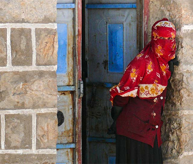 Yemeni culture: Village woman in a colorful red print headscarf is leaning stone wall in front of a blue door by Maarten de Wolf.