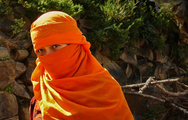 Yemeni clothing: A village woman in a colorful orange headscarf by Maarten de Wolf.
