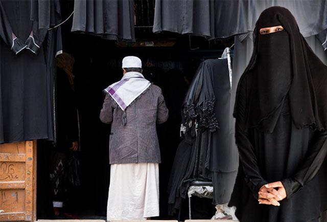 Yemeni clothing: A woman in a black balto and a man in traditional Yemeni clothing enters a balto shop by Maarten de Wolf.