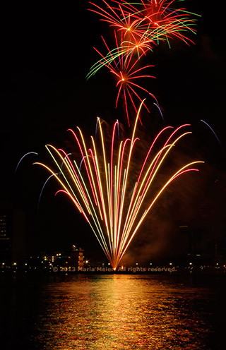 Multiple fireworks bursts reflected in the river by Marla Meier.