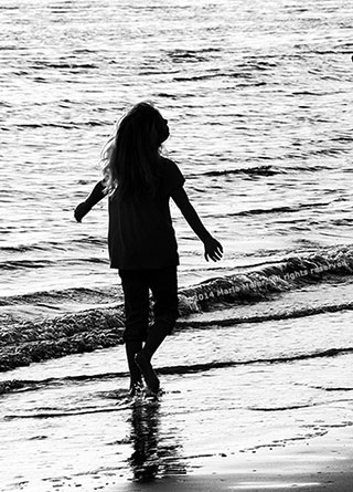 Black and white silhouette photo of a little girl dancing on the beach by Marla Meier.