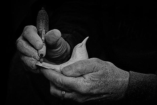 Black and white photo of a wood carver's hands carving a bird by Marla Meier.