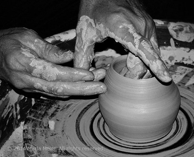 Black and white photo of a potter's hands spinning a clay pot on a potter's wheel by Marla Meier.