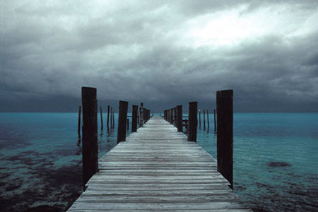 Photo of a boardwalk going into the sea where dock poles connect foreground with background by Gert Wagner.