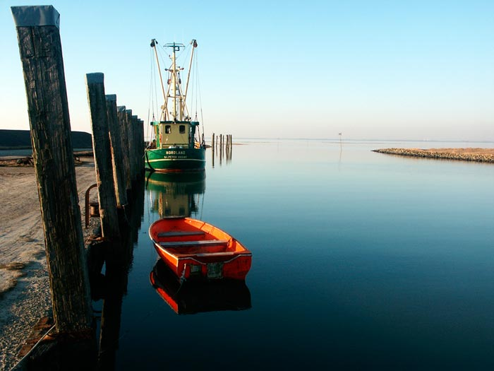 Photo showing left axis: dock with orange dingy and fishing boat on water by Gert Wagner.