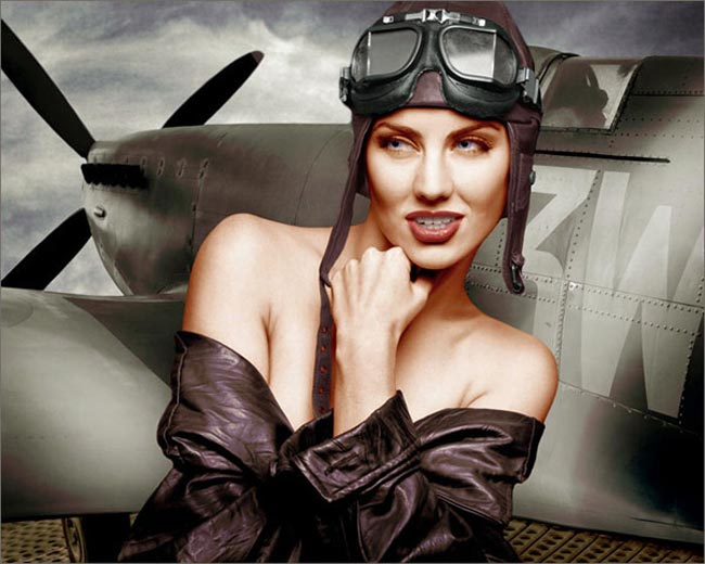 Photoshop colored photo of partially nude female model in retro style leather jacket and helmet in front of WWII plane from the retro series by Juul de Vries.