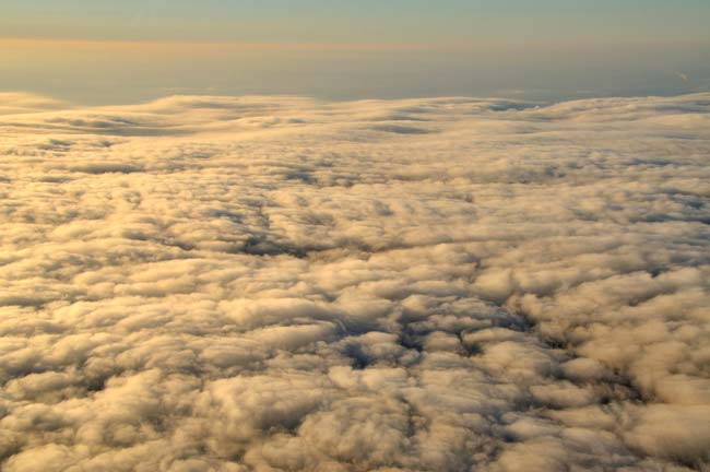 Aerial photo of the top of clouds with golden light by Allen Moore.