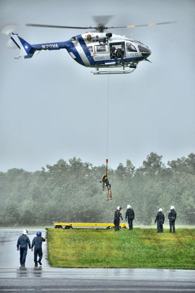 Aerial photography depicting vibration: photo of helicopter rescuing person by Allen Moore.