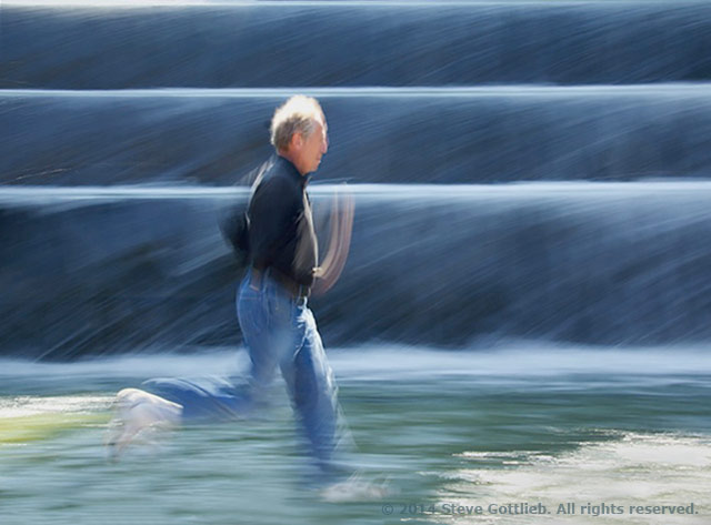Image of man running along water created by panning with the subject by Steve Gottlieb.