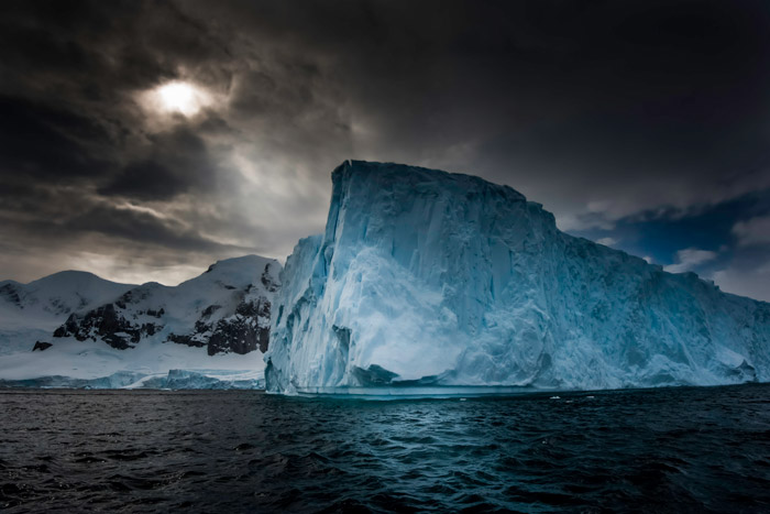 Photo of a blue-colored iceberg and dark cloudy sky in Antarctica by Michael Leggero.