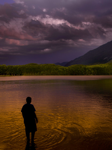 Man standing on edge of lake in Alaska by Michael Leggero.