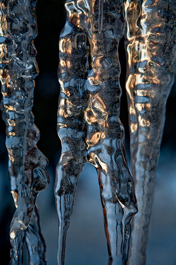 Macro photo of bluish, gold icicles showing reflected light, pattern and forms by Brad Sharp.