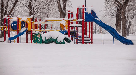 Photo of children's colorful playground equipment in the snow by Brad Sharp