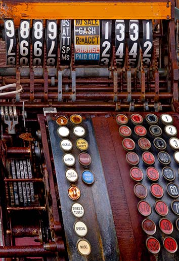 Close-up photo of an antique cash register with rows of colorful buttom by Brad Sharp