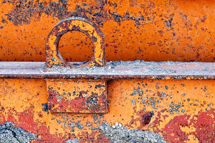 Macro photo of metal tie down loop on metal beam showing shades of orange and interesting textures and patterns in rust by Brad Sharp.