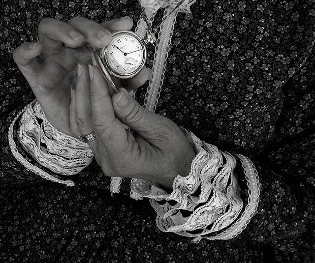 Image of hands holding an open pocket watch by Jim Austin.