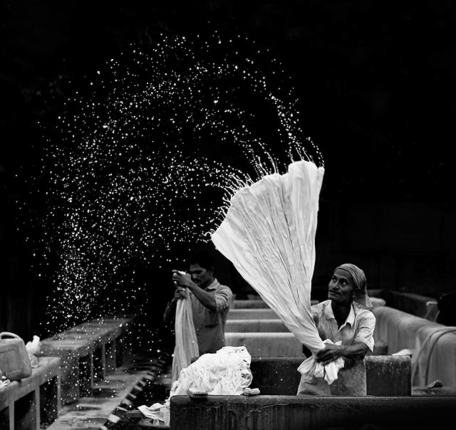 Black and white image of Mr. Spinner, a man in a Dhobighat in India, where people wash the clothes by G. Krupa Sindhu.