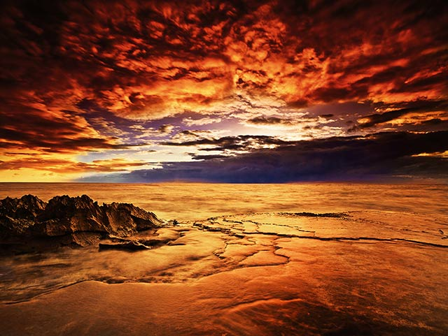Koholina: orange, red and gold seascape iimage made at sunset at the shore of Oahu, Hawaii by Jeff Mitchum.
