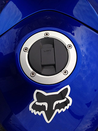 Detail of royal blue motorcycle gas tank captured by a smartphone camera by Allen Moore.