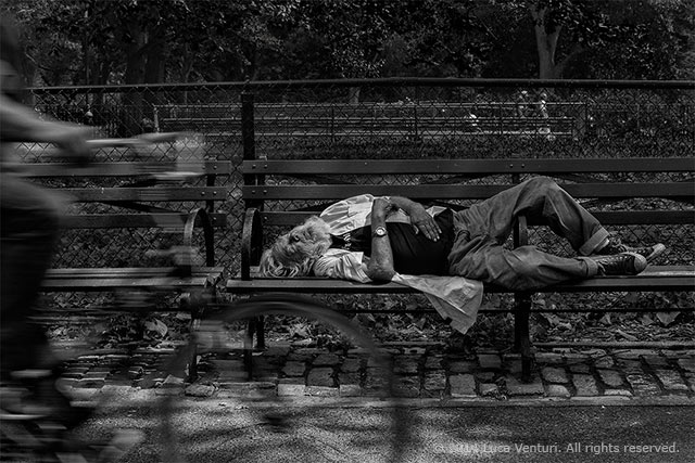 Black and white image of a vagrant sleeping on a park bench in the gardens of the square in New York City by Luca Venturi.