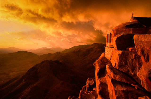 Landscape of mountain, foreground rocks adn structure with the golden, orange light of sunrise in Sinai, Egypt by Omar Attum.