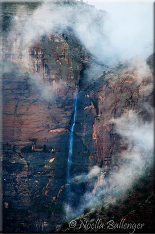 Image of a tall waterfall and storm coming in over rock formations in Zion National Park in Utah by Noella Ballenger.