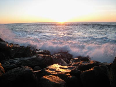 Image of California sunset over ocean waves and rocky shore by Marilyn S. Goerler.