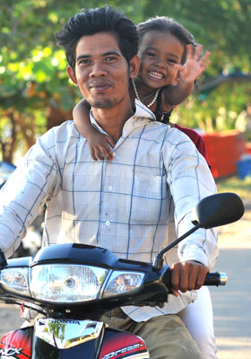 Photo of little girl & Dad on scooter by Ron Veto
