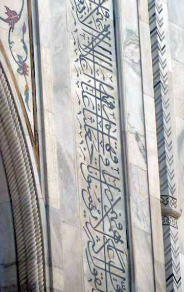 Close-up photo of the in-laid flowers and Koranic scripture on Taj Mahal by Rick Clark