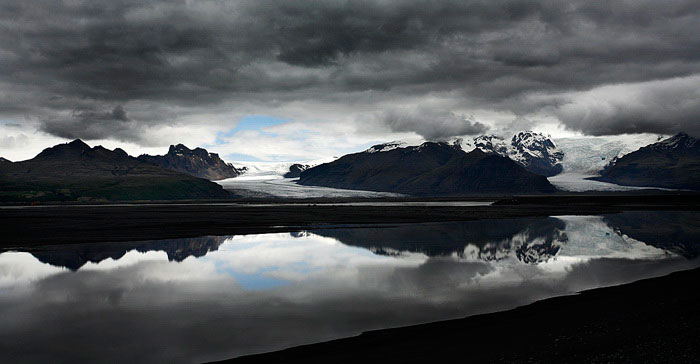 Image of storms clouds and mountains reflected on a lake in Iceland by Noella Ballenger.