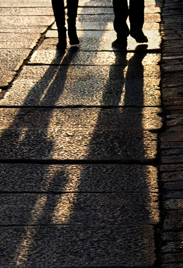 Image of long shadows of people walking in Helsinki, Finland by Noella Ballenger.